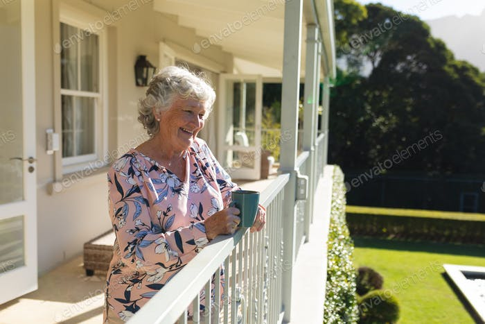 Senior caucasian woman standing on balcony holding mug and smiling