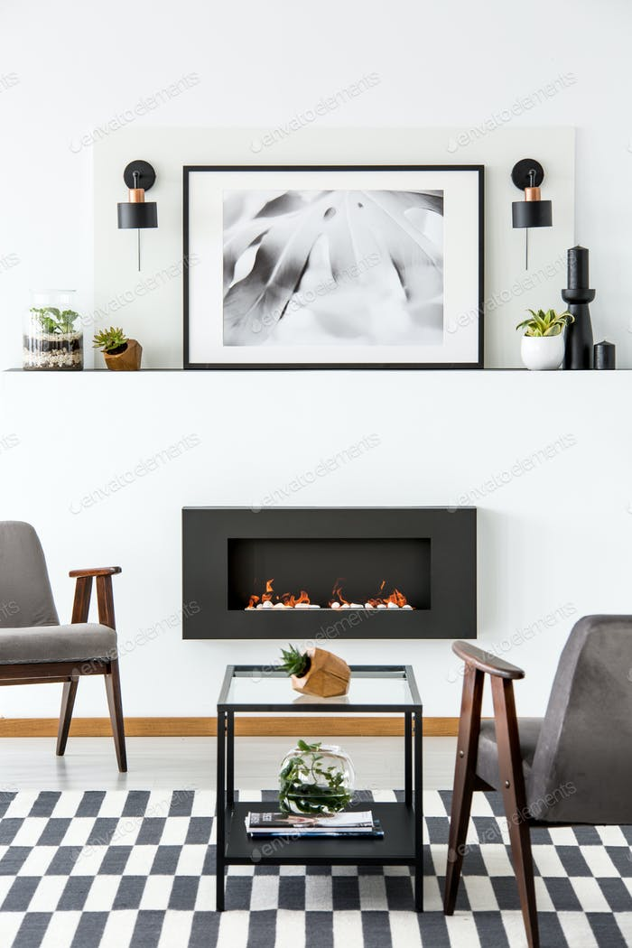 Poster above black fireplace in apartment interior with grey arm