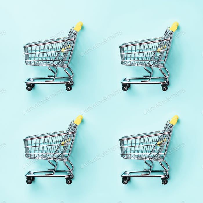 Shopping cart on blue background. Minimalism style. Creative design. Top view with copy space. Shop