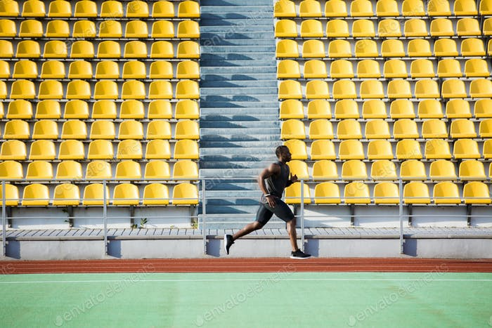 Full length side view of a sportsman running on racetrack