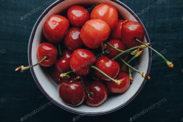 Cherries in bowl on black background