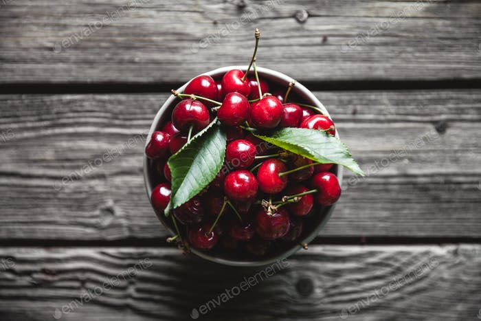 cherries on a dark wood background. toning. selective focus on cherry in the bowl