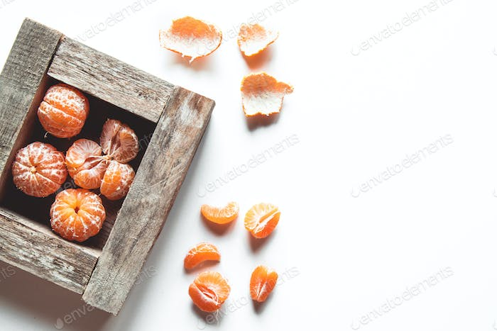 tangerines with fresh leaves in wooden box isolated on white, isolated on a white, top view