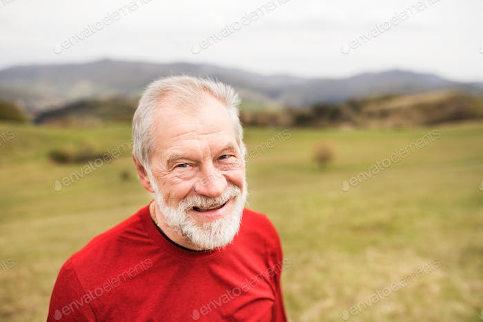 Active senior runner in red sweatshirt in nature resting.