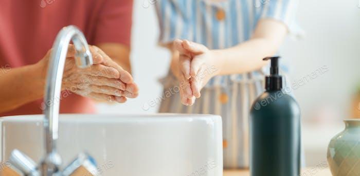 Mädchen und ihre Großmutter sind Händewaschen