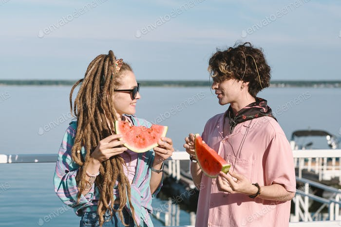 Happy young dates with slices of fresh juicy watermelon