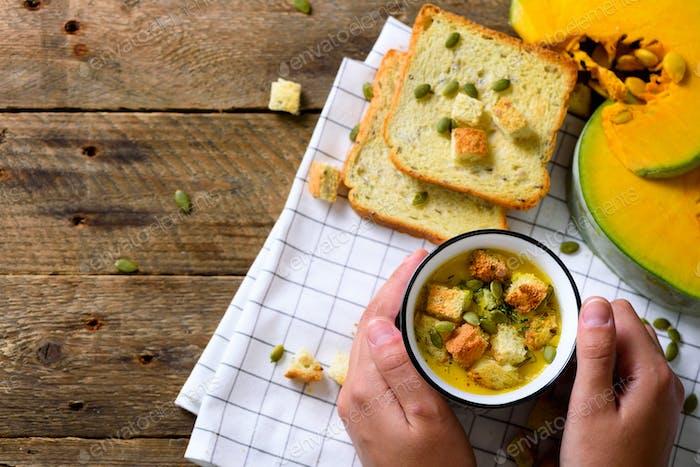 Tasse mit Karottencreme Suppe in Mädchen Hände mit Samen, Cracker auf Holz rustikalen Hintergrund, Kopie