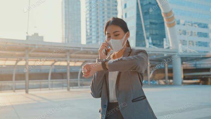 woman in fashion office clothe wear medical face mask talk via phone while walk alone.