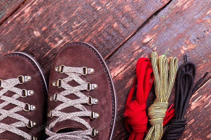 Brauner Mann Wildleder Stiefel und Schnürsenkel auf hölzernem Hintergrund. Flache Lag. Herbst- oder Winterschuhe.