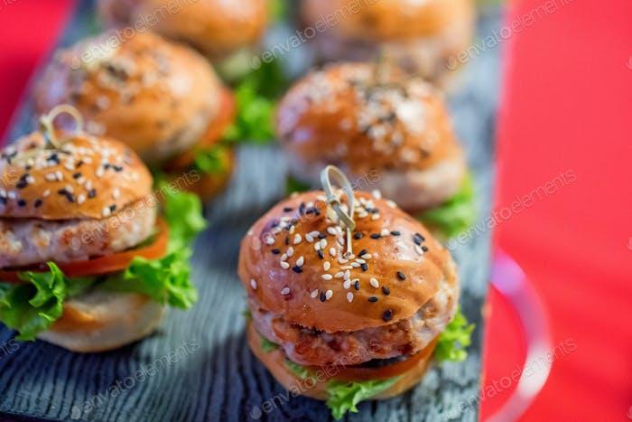 Leckere hausgemachte Mini-Hamburger auf Holzbrett schließen