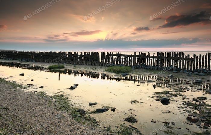 old breakwater on coast at sunset