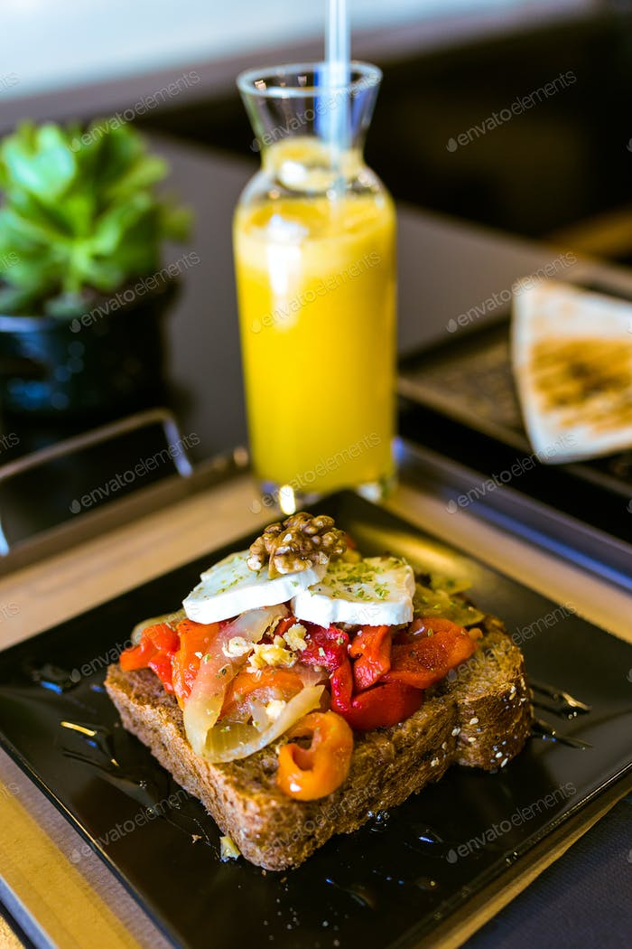 healthy sandwich with fruits and nuts and orange juice in a rest