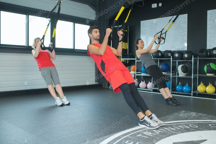 fit young people training hard at the gym - crossfit