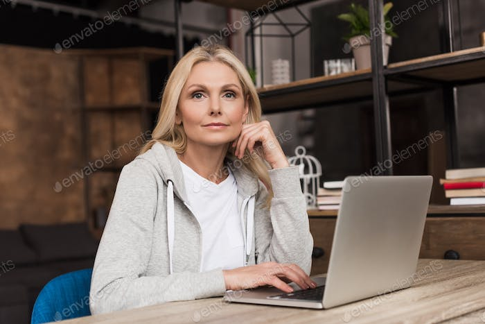 pensive middle aged woman using laptop at home