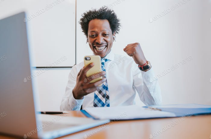 Businessman celebrating victory while looking at phone.