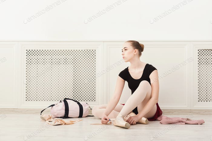 Ballerina puts on pointe ballet shoes,