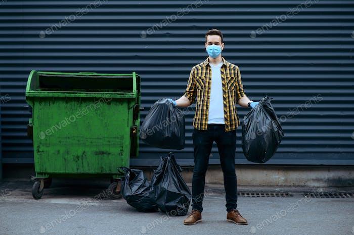 Volunteer in mask holds plastic trash bags