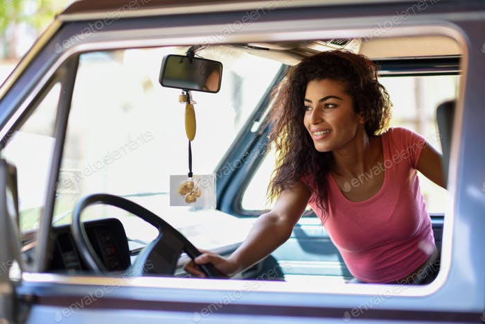 Arab girl inside an old van parked in a campsite in the middle o