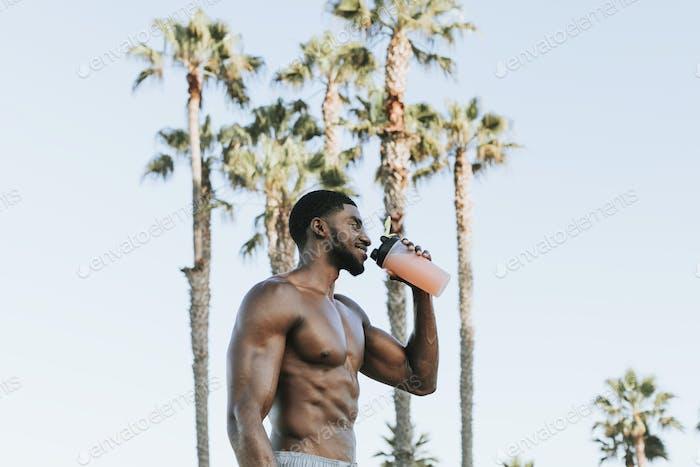 Muskulöser Mann, der einen Protein-Shake trinkt