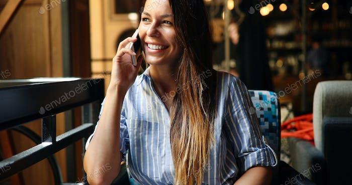 Beautiful woman talking on phone in restaurant