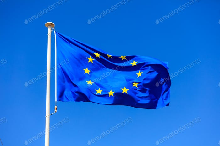 EU flag. European Union flag on a pole waving on blue sky background