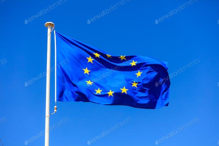 EU flag. European Union flag on a pole waving on blue sky background