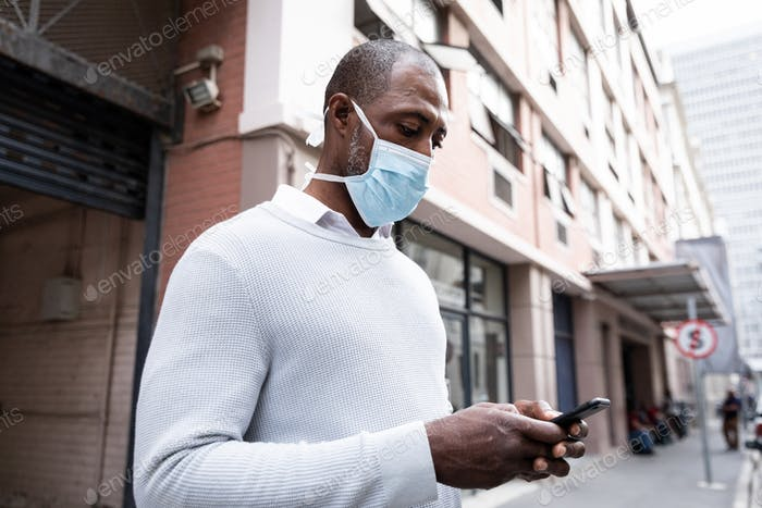 African American wearing covid19 coronavirus mask and using his phone in the street