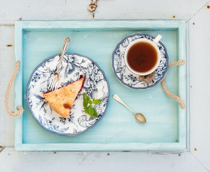 Piece of double crust plum pie and black tea in vintage porcelain cup, blue wooden tray