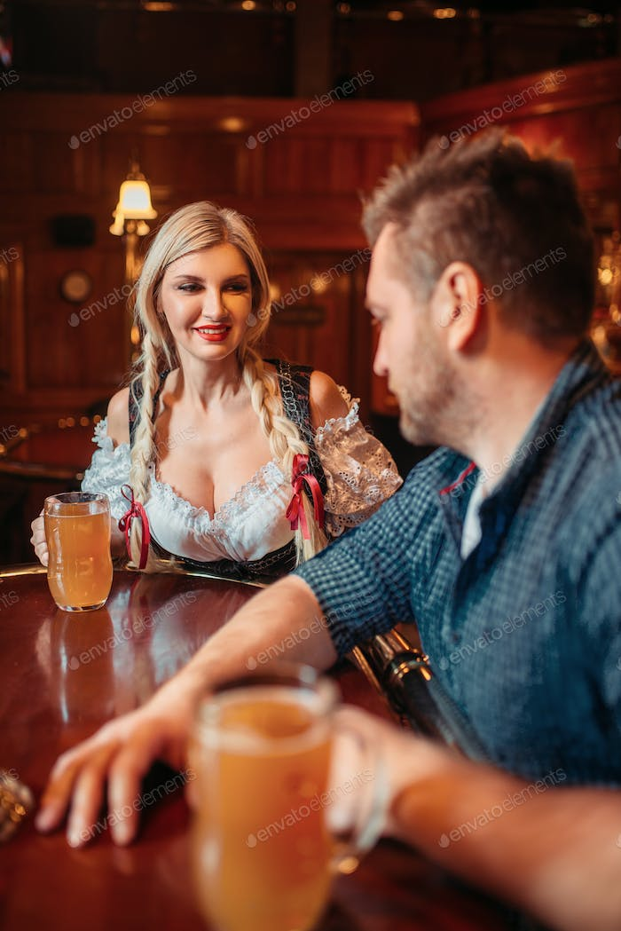 Drunk man with beer mug and waitress at counter