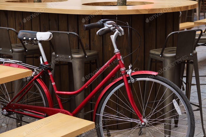 Close up photo of red classic bicycle in courtyard of cafe
