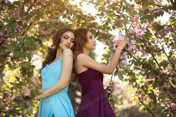 Fashion Portrait Photo of Two Women Near Blossoming Tree on Nature