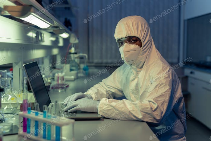 African male scientist in coveralls using laptop