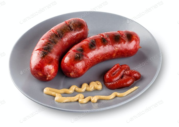 Sausages lying on gray  plate with mustard and ketchup