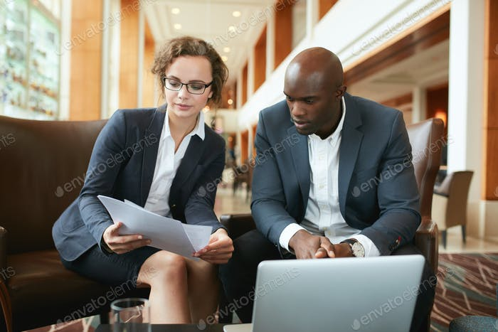Business people discussing papers in hotel lobby