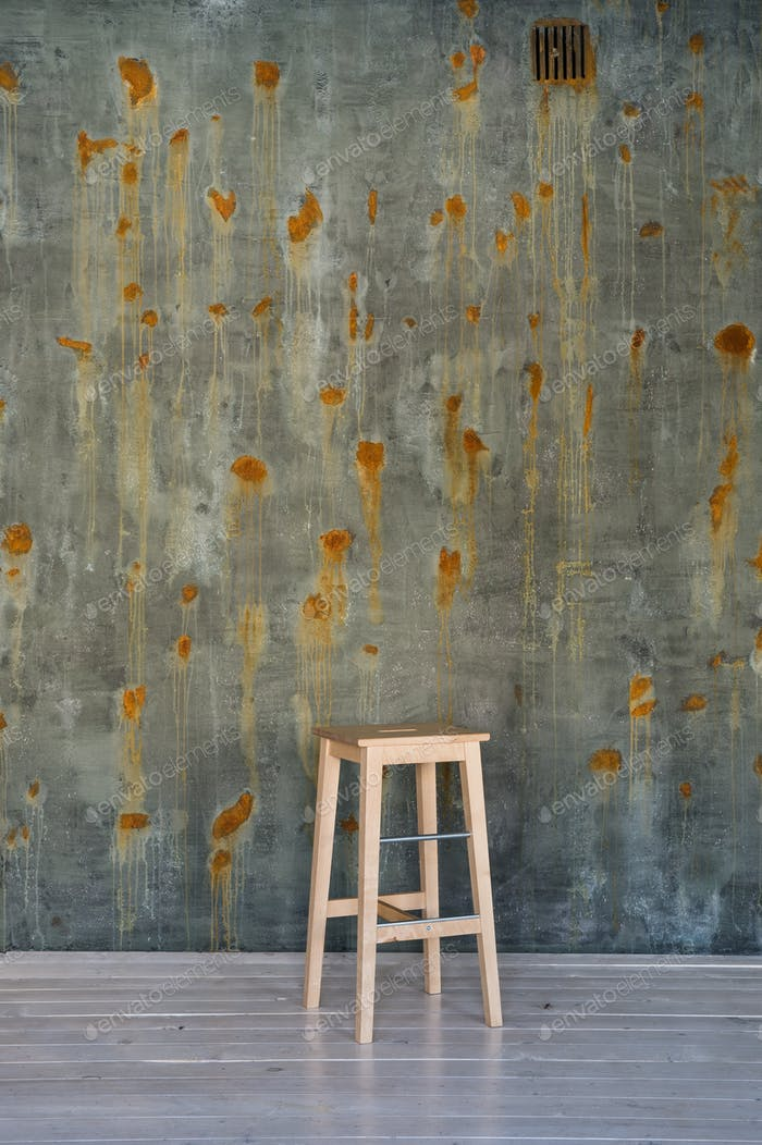 Bar stool chair on concrete wall with rust spots.