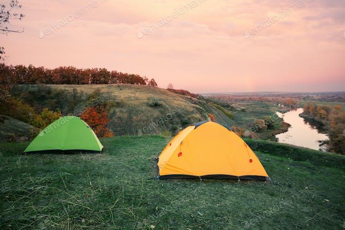 Camping von orangefarbenen und grünen Zelten am Ufer des Flusses