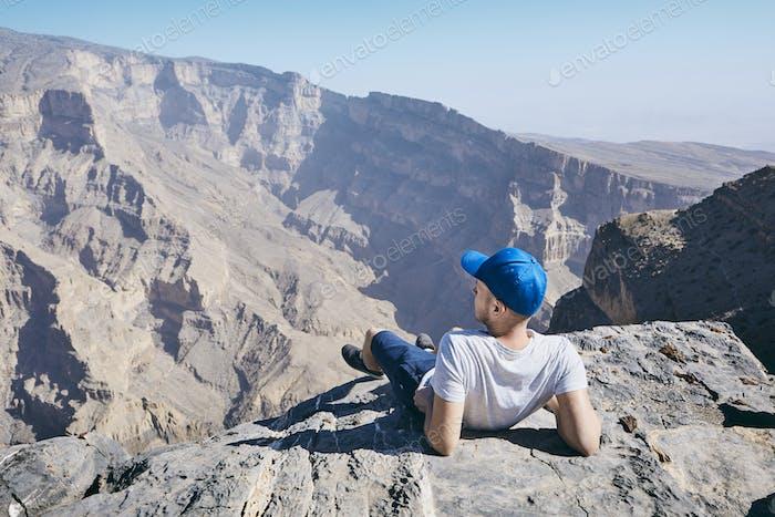 Tourist ruht am Rande der Klippe