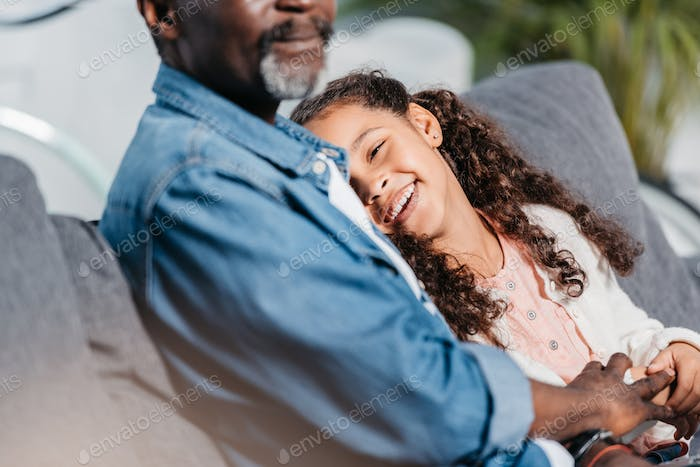 Portrait of african american father sitting together with daughter at home