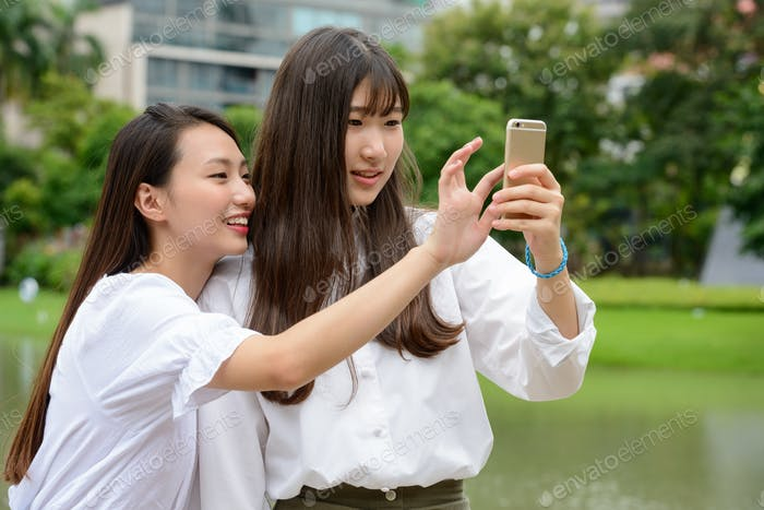 Two happy young beautiful Asian teenage girls taking selfie together at the park
