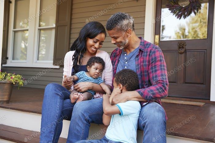 Familie mit Baby Sohn sitzen auf Stufen führen bis zur Veranda von zu Hause