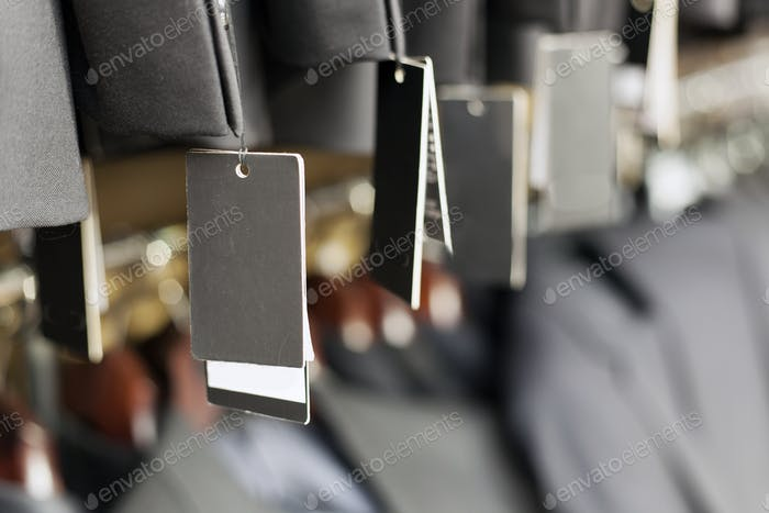 Blank label on elegant suit jacket hanging, apparel store