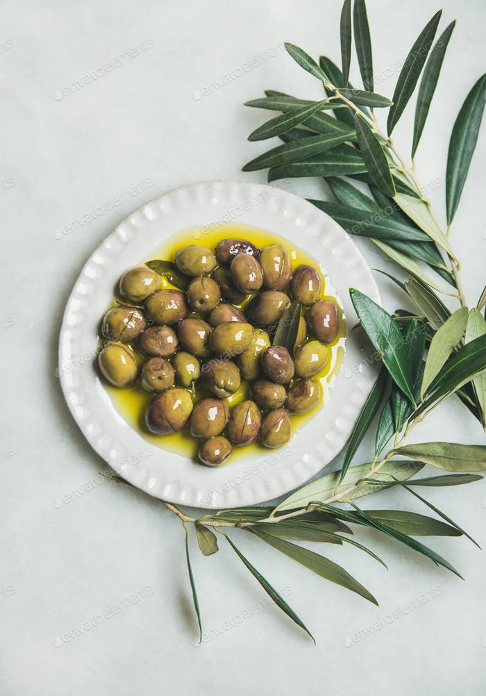 Pickled green olives and olive-tree branch over marble background
