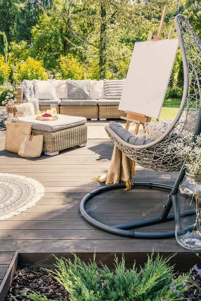Hanging chair on wooden patio with easel and rattan table in fro
