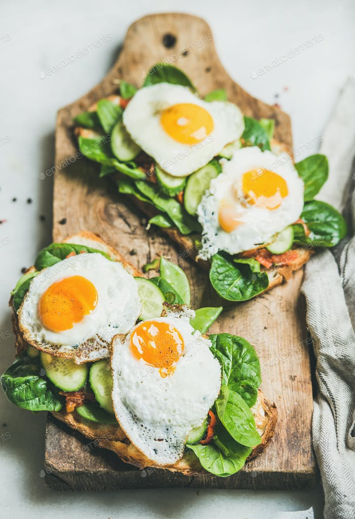 Healthy breakfast sandwiches on rustic wooden board over grey background