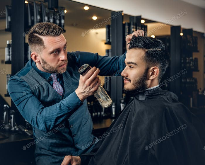 Hairdresser doing haircut to a bearded man in a barbershop.
