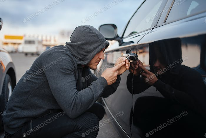 Car thief with screwdriver breaking door lock