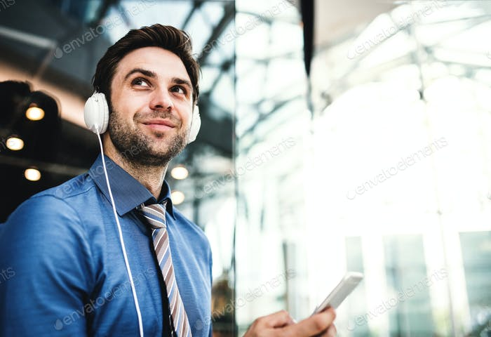 A young businessman with smartphone and headphones in a modern building.