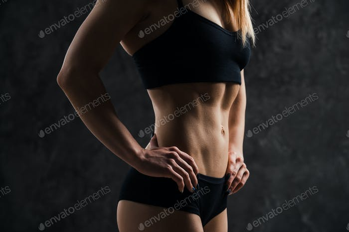 Side view of muscular fitness female model standing on black background.