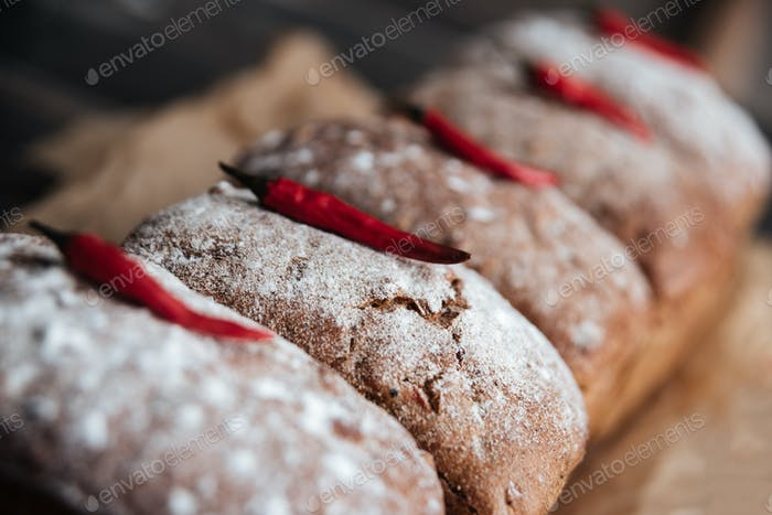 Bread with flour and pepper on dark wooden table