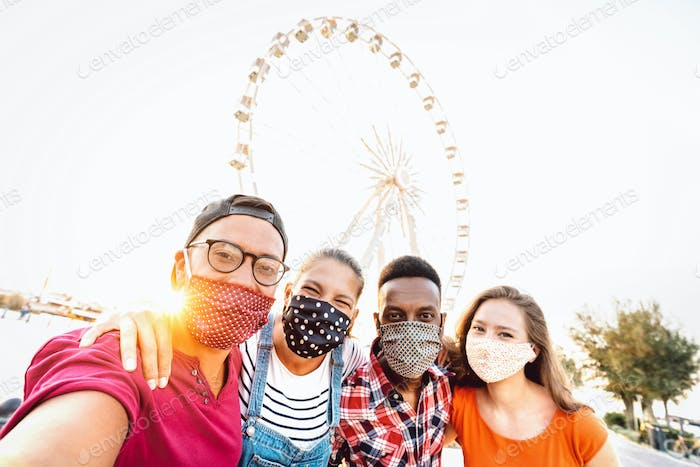 Multiracial milenial students taking selfie protected by face masks
